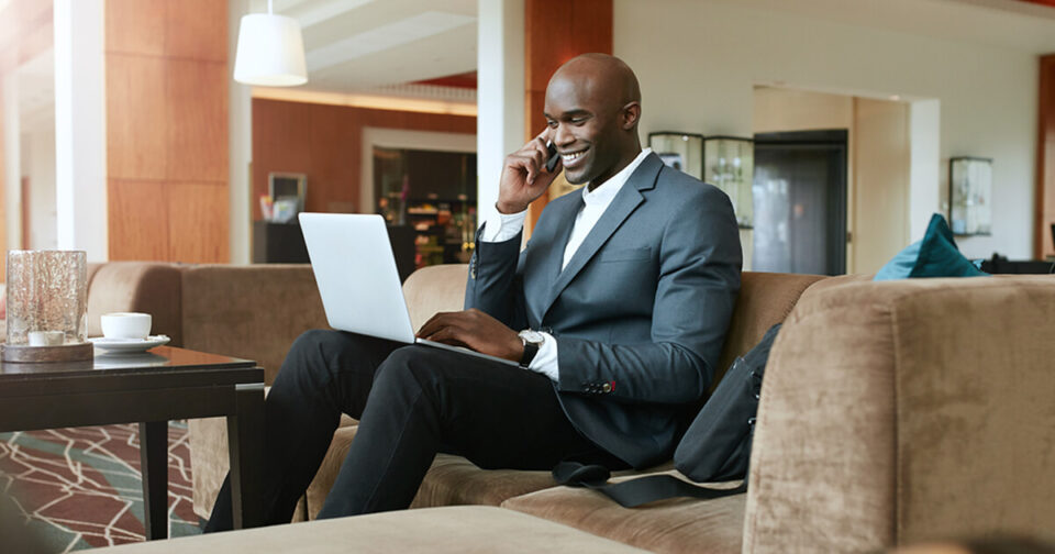 Man in a suit in a hotel lobby on his laptop